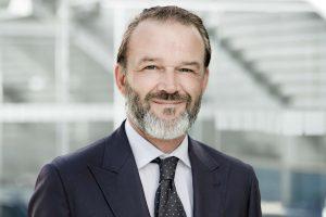 Portrait von Andri Bodmer von der SQS im dunklen Anzug mit gepunkteter Krawatte