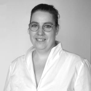 Portraitfoto von Astrid Benedik mit Brille in einer Bluse in schwarz weiß