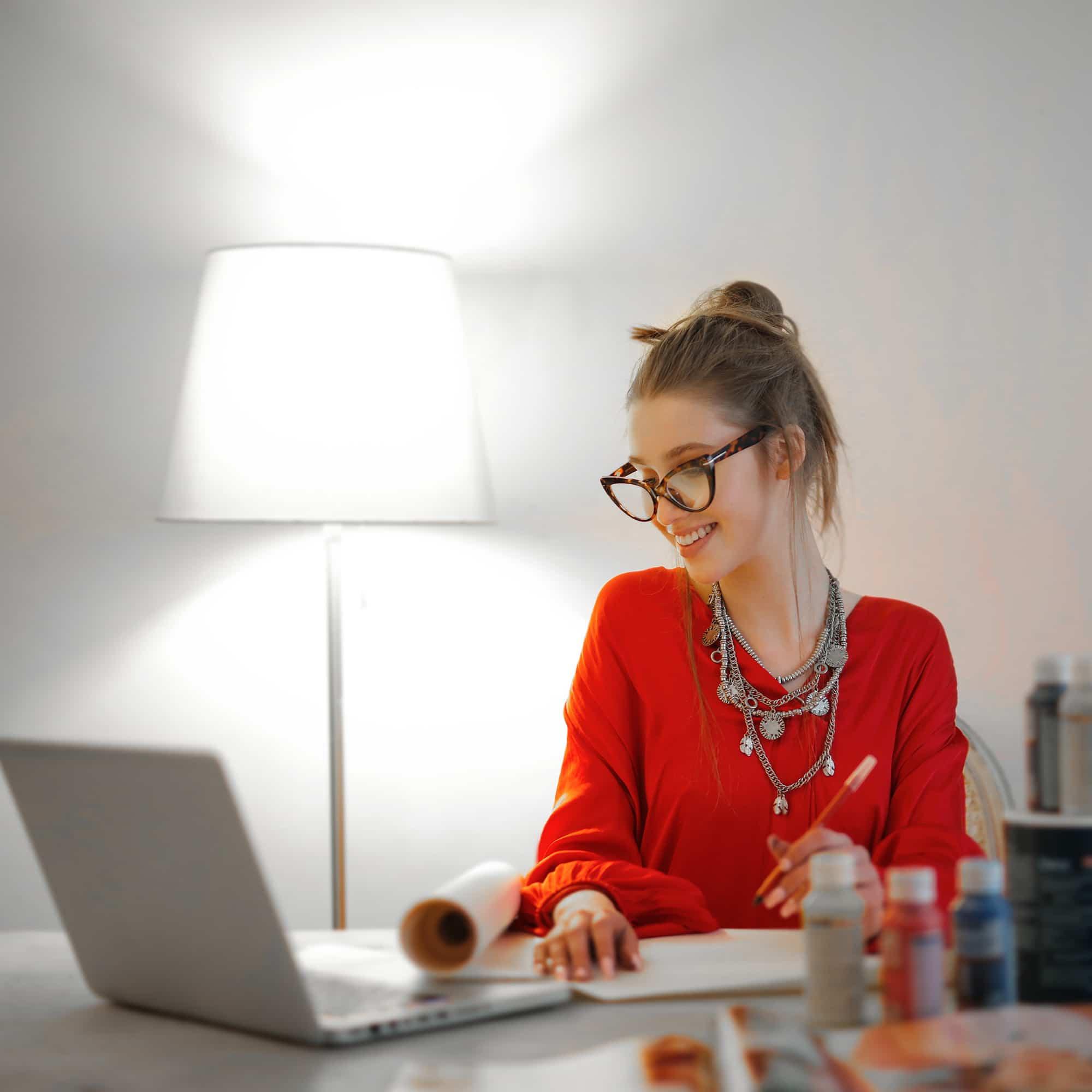 Glückliche Frau in rotem Pullover arbeitet am Laptop