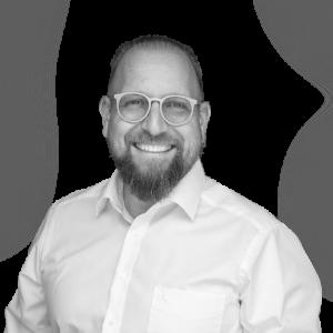 Portraitbild von Netzwerkpartner Wolfgang Gliebe lächelnd mit Brille im Hemd quadratisch schwarz weiß